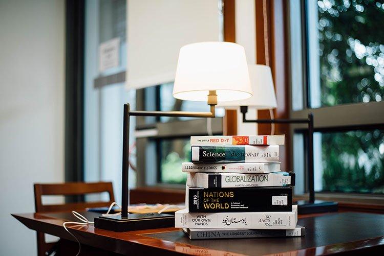 چندین کتاب چیده شده روی میز