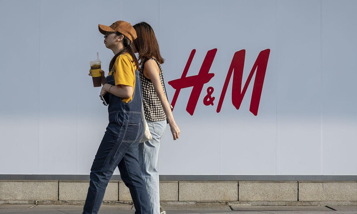 تصویر دو دختر در کنار تصویر تبلیغاتی h&m